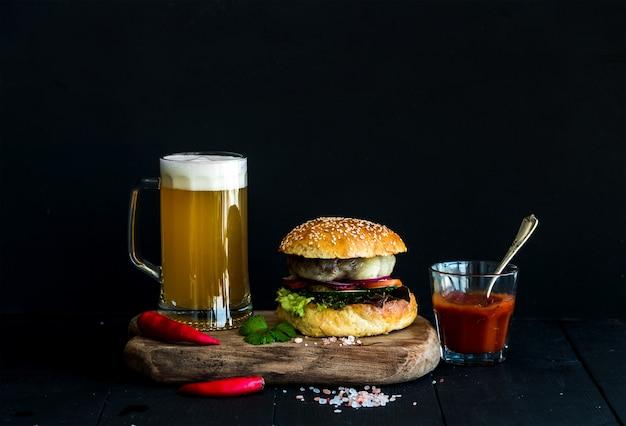 Hamburguesa casera fresca sobre tabla de servir de madera con salsa de tomate picante, sal marina, hierbas y jarra de cerveza ligera