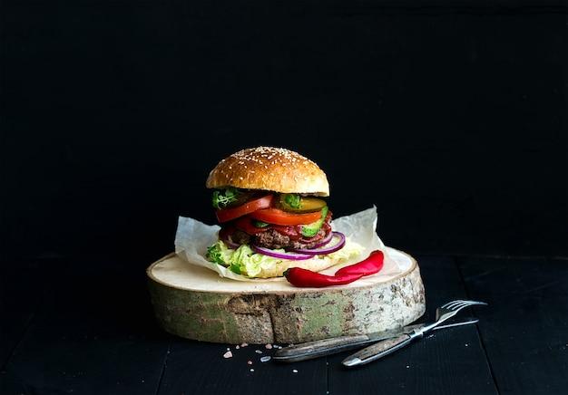 Hamburguesa casera fresca en tablero de madera con salsa de tomate picante, sal marina y hierbas sobre fondo negro.