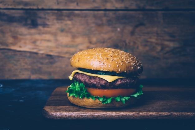 Hamburguesa casera (hamburguesa con queso) con carne sobre un fondo de madera. hamburguesa casera clásica.
