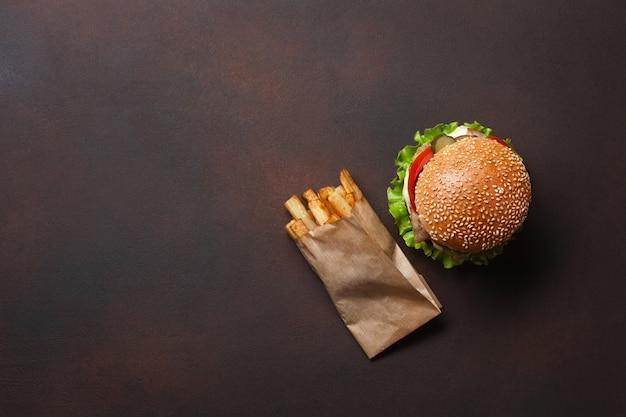 Hamburguesa casera con ingredientes de carne de res, tomates, lechuga, queso, cebolla, pepinos y papas fritas sobre fondo oxidado