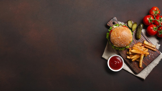 Hamburguesa casera con ingredientes de carne de res, tomates, lechuga, queso, cebolla, pepinos y papas fritas en la tabla de cortar y fondo oxidado