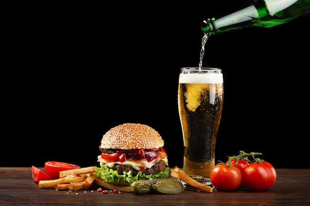 Hamburguesa casera con papas fritas y una botella de cerveza vertiendo en un vaso.