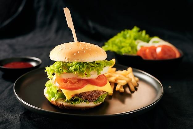 Hamburguesa casera sabrosa fresca en una placa negra