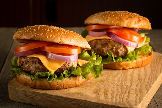 Hamburguesa casera con ternera, cebolla, tomate, lechuga y queso. hamburguesa fresca de cerca en la mesa rústica de madera con papas fritas, cerveza y patatas fritas. hamburguesa con queso.