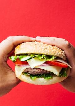 Hamburguesa con cebolla y queso sobre fondo rojo.