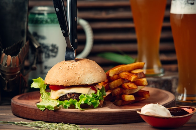 Hamburguesa clásica con papas fritas y cerveza.