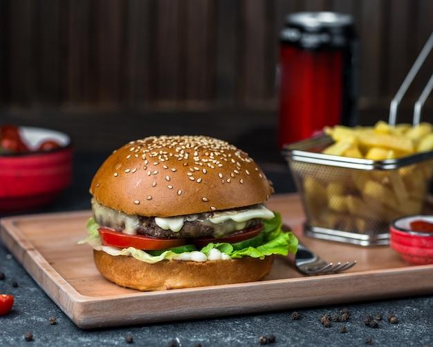 Hamburguesa con cotlet, verduras y salsa de mayonesa.