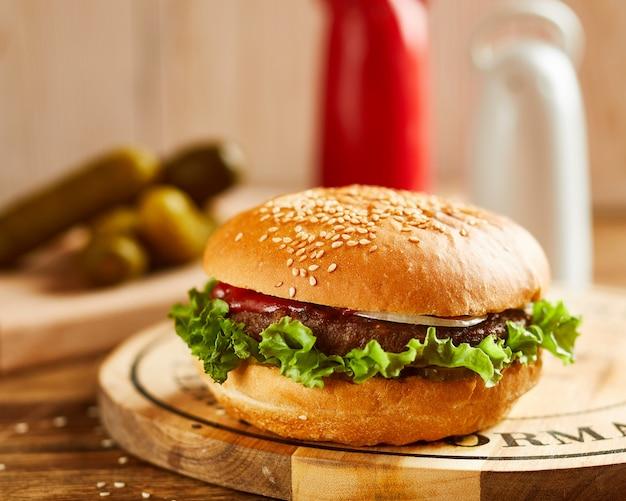 Hamburguesa deliciosa fresca, servida sobre tabla de madera
