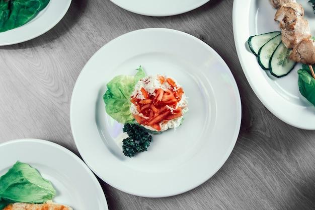 Hamburguesa, ensalada de verduras y otros platos en la mesa del restaurante. comida rápida