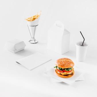 Hamburguesa fresca papas fritas; parcelas y vaso de disposición sobre fondo blanco