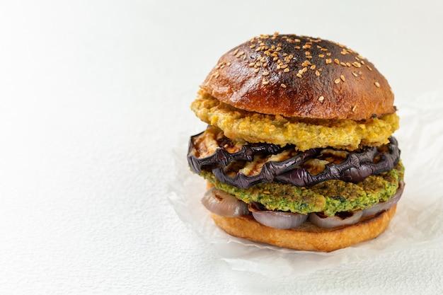 Hamburguesa de garbanzos vegana fresca con cebolla y berenjenas a la parrilla. el concepto de comida sana y vegetariana. lugar para el texto.