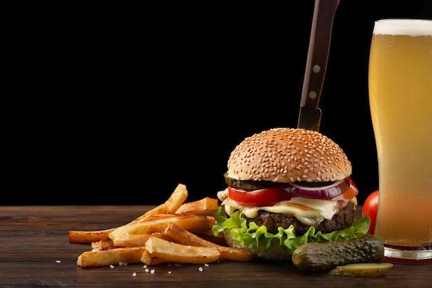 Hamburguesa hecha en casa con las patatas fritas y el vidrio de cerveza en la tabla de madera. en la hamburguesa se clavó un cuchillo.