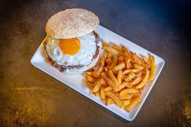 Hamburguesa con huevo frito y papas fritas sobre un fondo negro, sobre una placa blanca.
