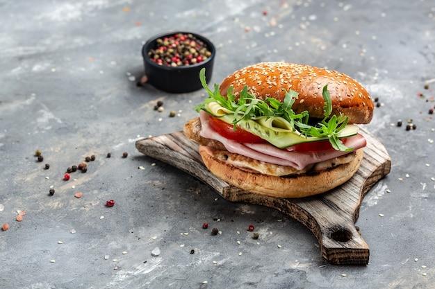 Hamburguesa con jamón, tomate y lechuga, comida rápida americana. banner, menú, lugar de recetas para texto, vista superior