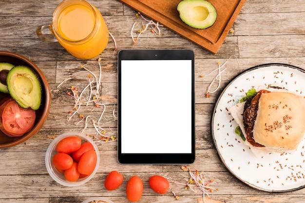 Hamburguesa; jarra de jugo; los tomates aguacate y brote y tableta digital en mesa de madera.