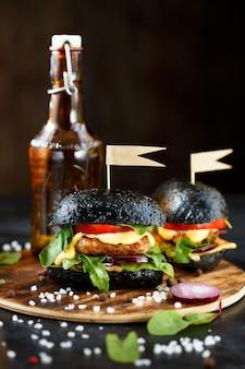 Hamburguesa negra con chuleta, verduras, queso, cebolla y tomate y una botella de cerveza en un plato de madera