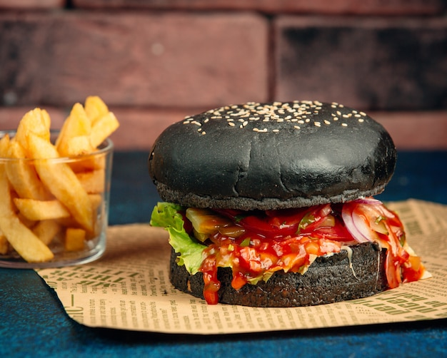 Hamburguesa negra con salsa de tomate, lechuga, cebolla, tomate y papas fritas.