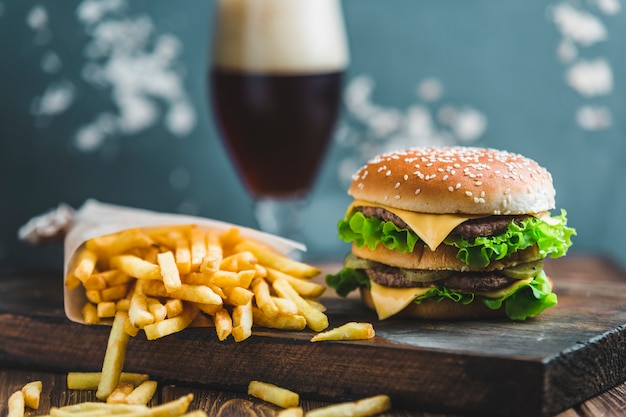 Hamburguesa con papas y cerveza oscura en una tabla de madera sobre un fondo azul-gris