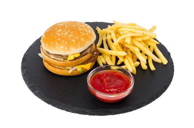 Hamburguesa y papas fritas, ketup en placa negra