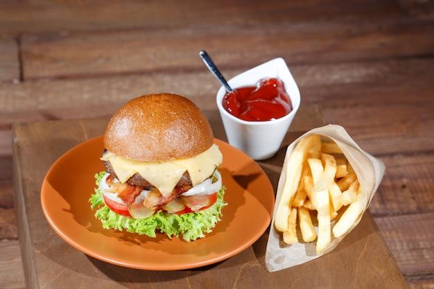 Hamburguesa y papas fritas en la mesa de madera.