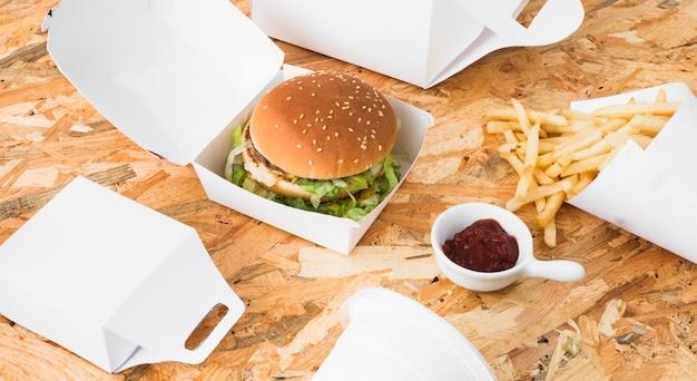 Hamburguesa; papas fritas y paquete de alimentos se burlan sobre fondo de madera
