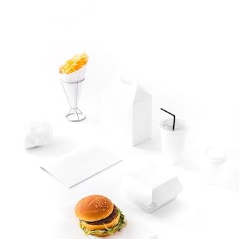 Hamburguesa; papas fritas; paquete desechable de bebidas y papel sobre fondo blanco.