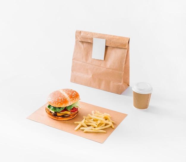 Hamburguesa; papas fritas; paquete y vaso de disposición en superficie blanca