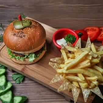 Hamburguesa con papas fritas, pepino, tomate y salsa.