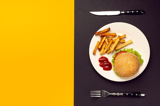 Hamburguesa y papas fritas en placa con espacio de copia