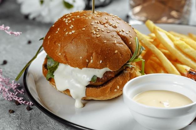 Hamburguesa con papas fritas y salsa en un plato blanco.