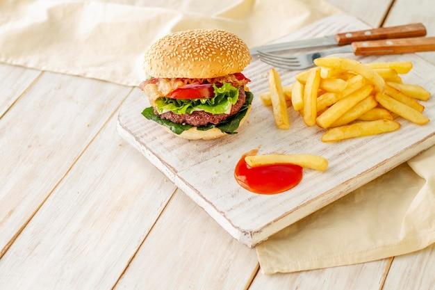 Hamburguesa con papas fritas y salsa sobre tabla de madera
