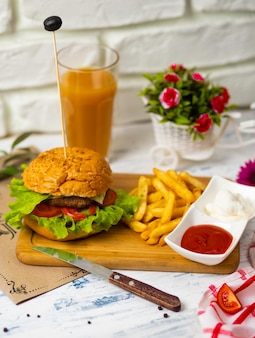 Hamburguesa con papas fritas sobre tabla de madera con salsa de tomate y mayonesa, cocina