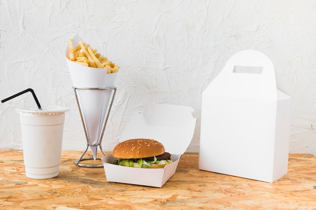 Hamburguesa; papas fritas; taza de eliminación y paquete de comida maqueta en la mesa de madera