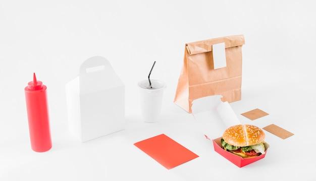 Hamburguesa; paquete; salsa botella y vaso desechable sobre superficie blanca.