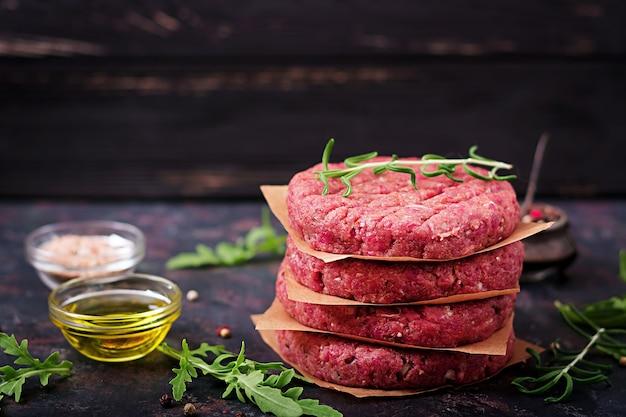 Hamburguesa picada hecha en casa cruda fresca del filete de carne de vaca con las especias en fondo negro.