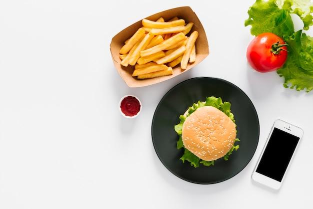 Hamburguesa plana y papas fritas en un plato con copyspace