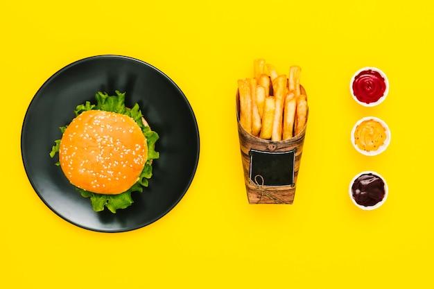 Hamburguesa plana con papas fritas y salsas.