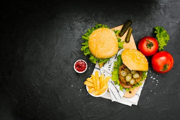 Hamburguesa plana y papas fritas sobre tabla de madera con copyspace