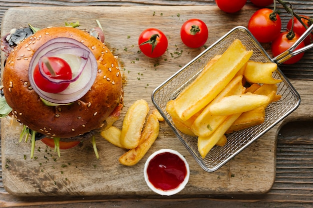 Hamburguesa plana y papas fritas sobre tabla de madera
