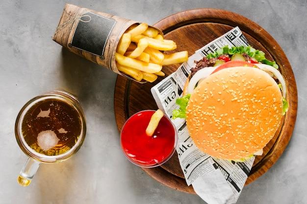 Hamburguesa plana sobre tabla de madera con papas fritas y cerveza.