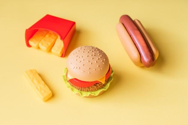 Hamburguesa de plástico, ensalada, tomate, freír papas con un hot dog sobre un fondo amarillo.