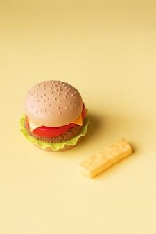 Hamburguesa de plástico, ensalada, tomate, sobre un fondo amarillo