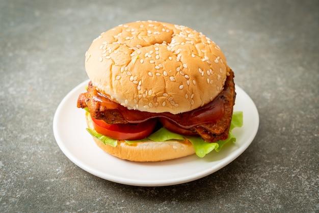 Hamburguesa de pollo asado con salsa en la placa blanca.