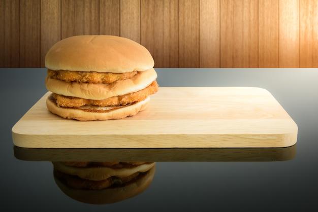 Hamburguesa de pollo, tabla de cortar de madera con reflejos, espacio vacío para su texto