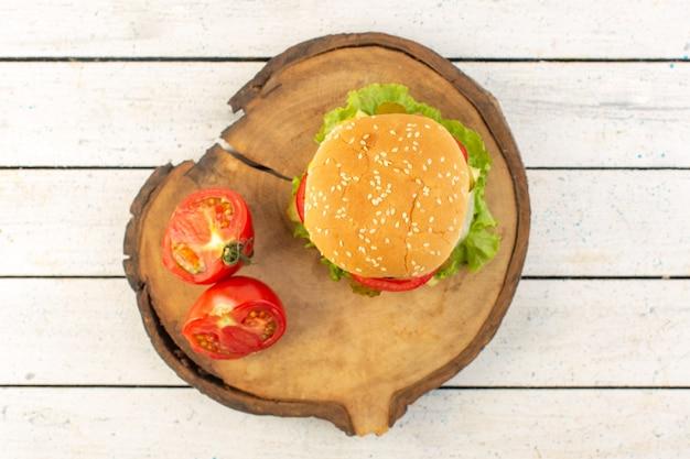 Una hamburguesa de pollo vista superior con queso y ensalada verde