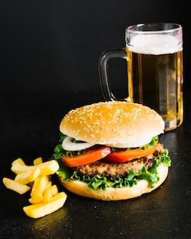 Hamburguesa de primer plano de alto ángulo con papas fritas y cerveza