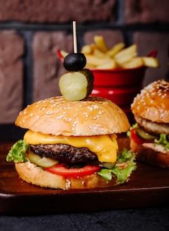 Hamburguesa con queso en bollo de pan con aceitunas en la parte superior.