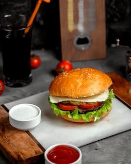 Hamburguesa con queso y carne con pepinillos y tomates