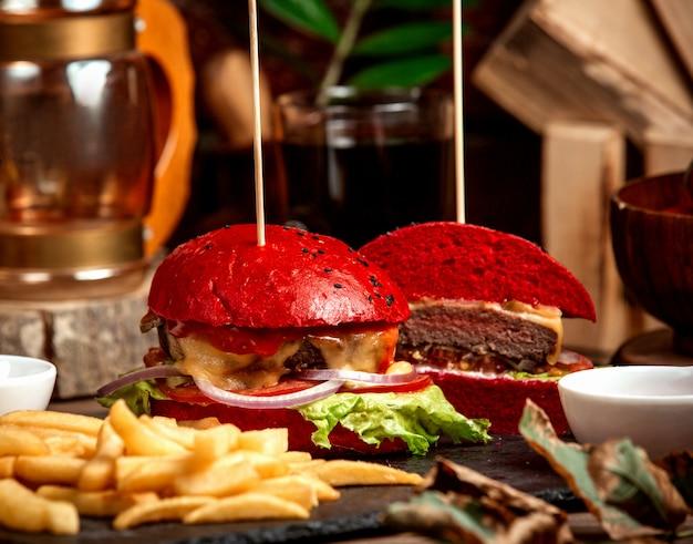 Hamburguesa con queso con pan rojo y papas fritas