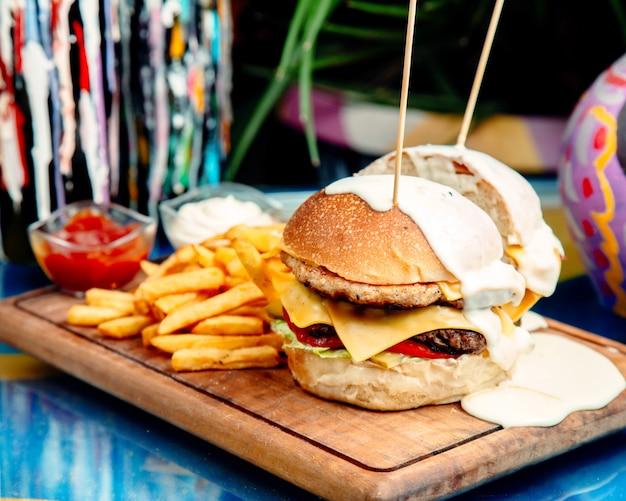Hamburguesa con queso con papas fritas en la mesa